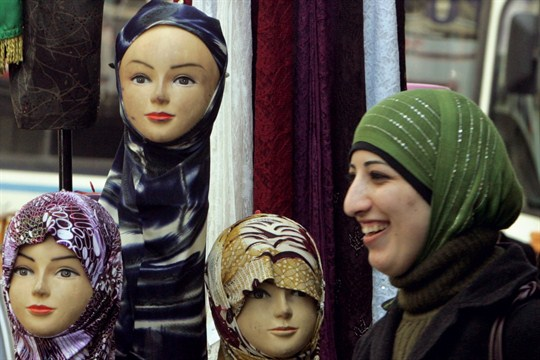 A Palestinian woman walks by a display of Islamic headscarves for sale in Ramallah.