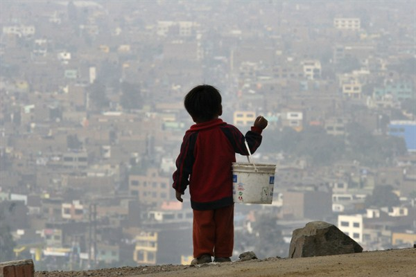 A child holds a bucket as he stands at the top of a hill in Lima.
