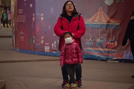 A woman helps a child wear a mask to protect against air pollution, Beijing, China