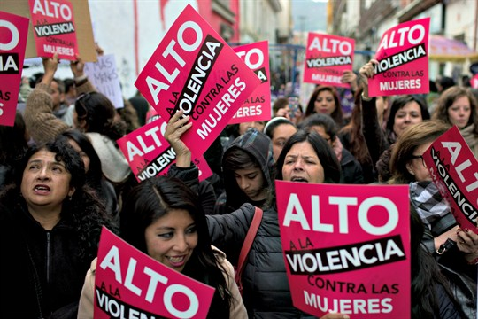 "Activists with signs that read in Spanish, ""Stop violence against women."