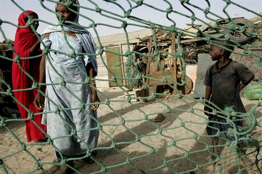 Two women and a boy seen through a chain-link fence in Mauritania.