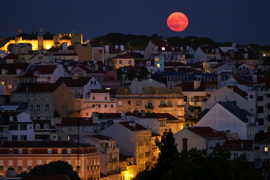 The full moon rises behind the Castle of Saint George in Lisbon, Portugal.