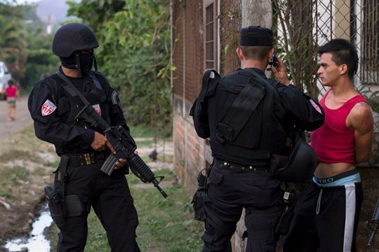 A suspected gang member being detained by two policemen in El Salvador.