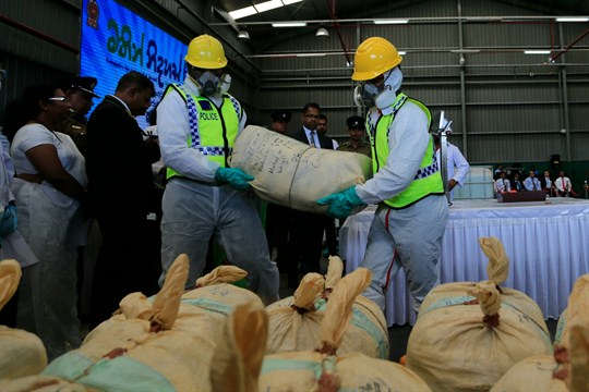 Sri Lankan police officers in protective costumes prepare to destroy a haul of seized cocaine.