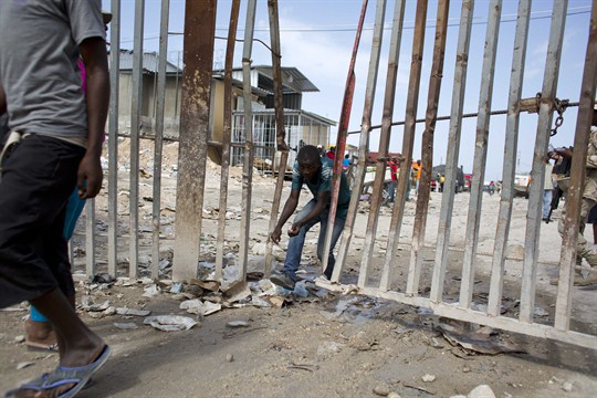 A Haitian worker crosses a border fence separating Haiti and the Dominican Republic.