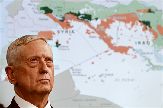 U.S. Defense Secretary Jim Mattis in front of a map of Syria and Iraq.