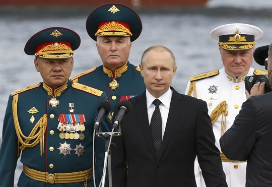 Russian President Vladimir Putin, flanked by top officials, attends a military parade during Russia's Navy celebration.