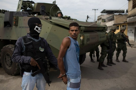 A masked Brazilian police officer holds a suspect in handcuffs in Rio de Janeiro.