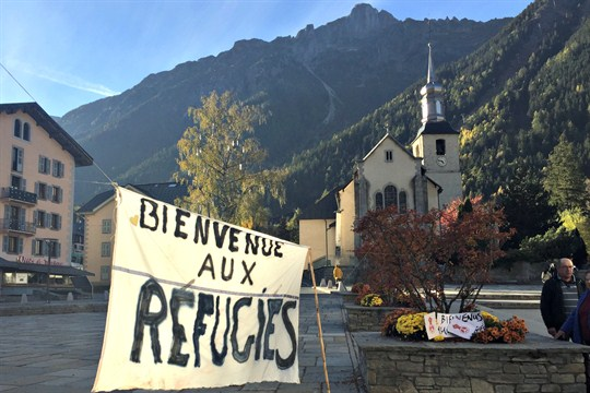 "A banner in a town square in the French Alps reads ""Welcome Refugees."