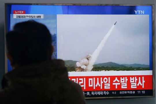 A man watches a TV news program showing footage of a North Korean missile launch.