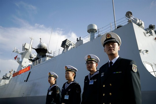 Chinese naval officials stand in front of the ship Daqing, in San Diego.