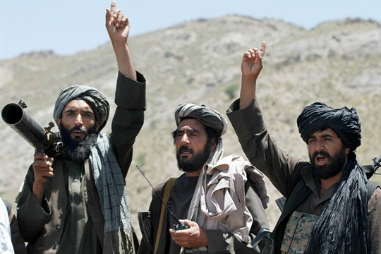 Taliban fighters raise their hands in reaction to a speech by their senior leader.