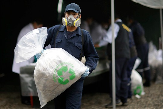 A city employee carries a bag of seized cocaine to be destroyed in Lima, Peru.