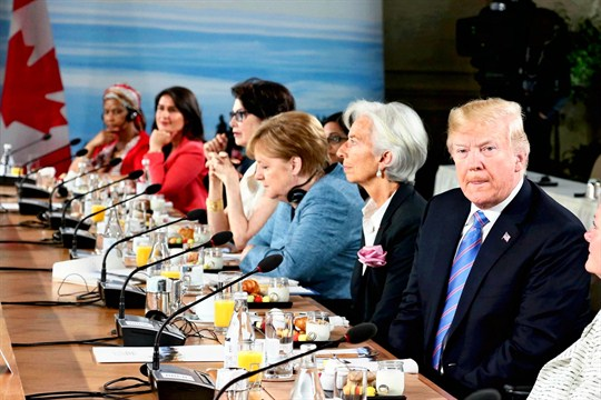 Donald Trump sitting at a table next to Christine Lagarde, Angela Merkel, and others at meeting.