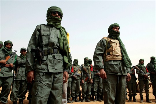 Troops stand with former rebels involved in the ongoing Malian conflict before a joint patrol.