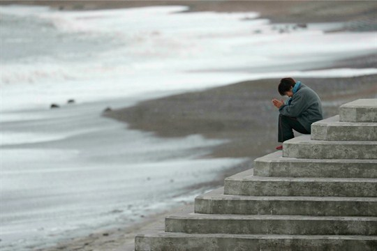 A woman prays at a beach near the sight of the Fukushima nuclear disaster.