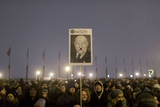 A poster mocking Viktor Orban held on a stick above protesters' heads.