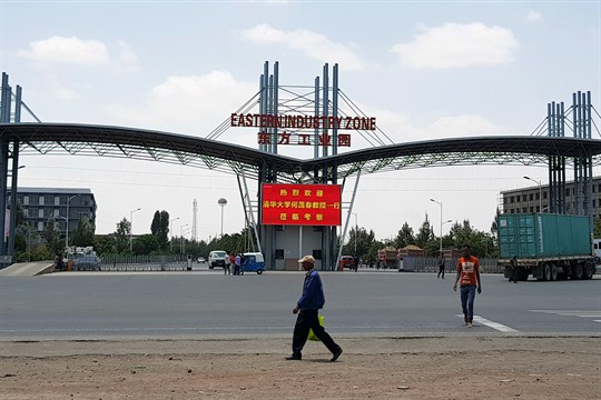 People walking past the gate of a Chinese factory in Ethiopia.