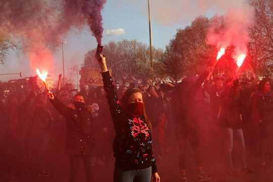 A woman holding a red flare in the air at a women's rights march.
