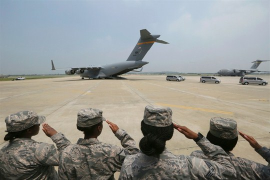 U.S. soldiers seen from behind saluting, with a cargo plane in the background.