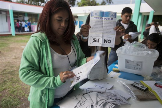 An electoral worker displays a ballot concerning a border dispute between Belize and Guatemala.