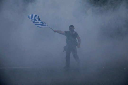 A protester waves a Greek flag during clashes in the city of Thessaloniki in 2018.