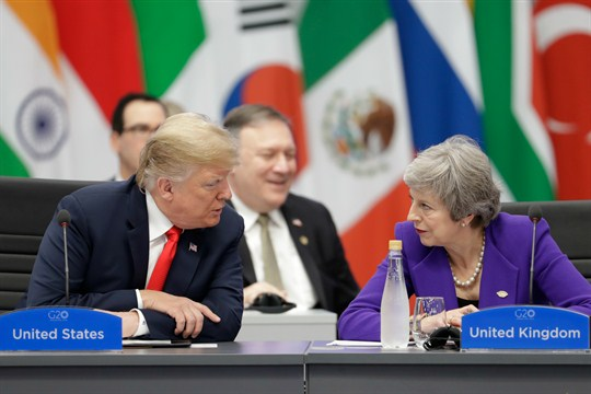 British Prime Minister Theresa May listens to U.S. President Donald Trump.