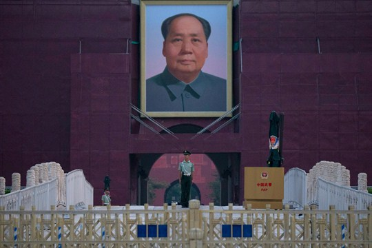 A Chinese paramilitary policeman stands guard in front of Mao Zedong's portrait on Tiananmen Gate.