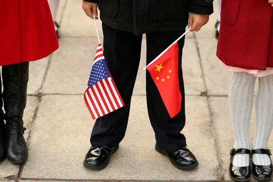 A person holds Chinese and American flags before a welcome ceremony with presidents Trump and Xi.