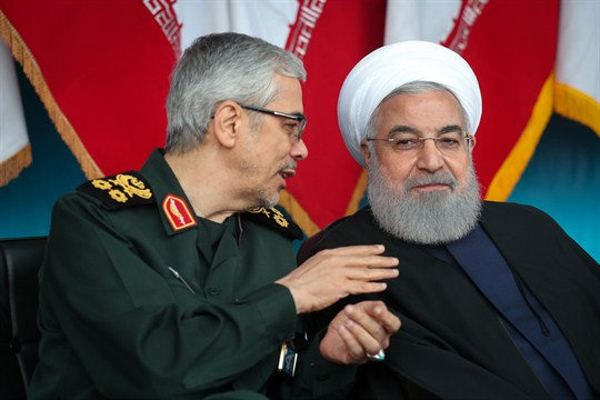 Iranian President Hassan Rouhani listens to Gen. Mohammad Hossein Bagheri during an army parade outside Tehran.