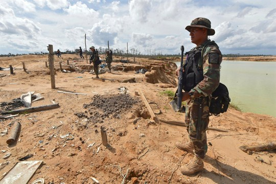 Peruvian police officers stand guard in a recovered area deforested by illegal gold mining in Peru.