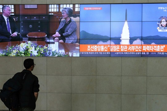 A man watches TV screens showing North Korean weapons systems in Seoul.