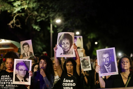 Demonstrators hold photos of persons who were killed during Brazil's dictatorship during a protest.