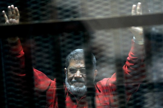 Former Egyptian President Mohammed Morsi raises his hands inside a defendant's cage in a makeshift courtroom.