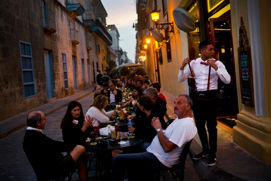 A waiter serves customers at a private restaurant in Havana.
