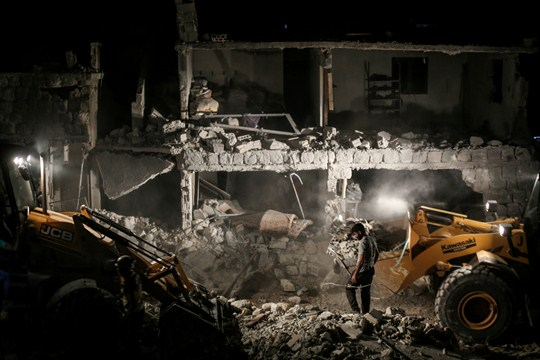 A member of the Syrian Civil Defense searches for survivors in a collapsed residential building.
