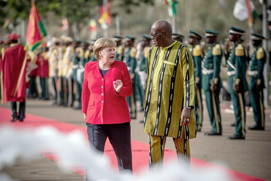 German Chancellor Angela Merkel is greeted with military honors by Burkina Faso's president, Roch Kabore.