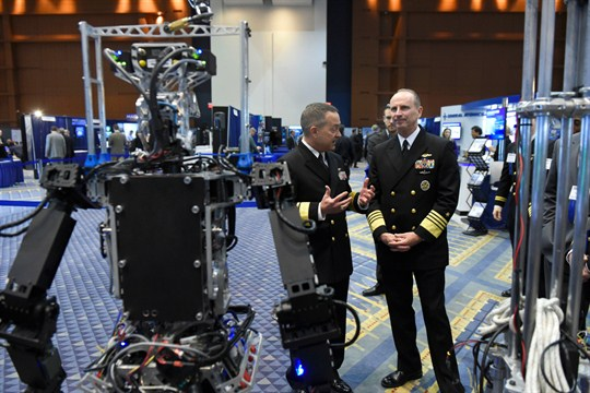 Two U.S. Navy admirals standing with the Navy-sponsored Shipboard Firefighting Robot.
