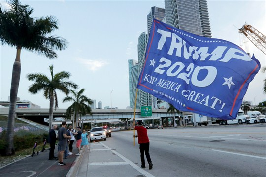 A Trump supporter waves a flag in Miami outside the venue for the Democratic presidential debates.