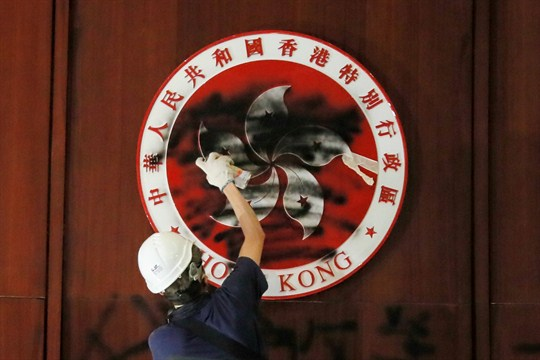 A protester defaces the Hong Kong emblem after they breaking in to the Legislative Council building.