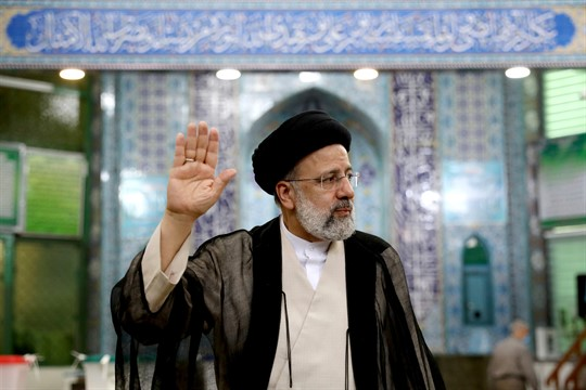 Iranian President Ebrahim Raisi waves to the media after casting his vote at a polling station.