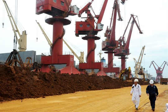Chinese inspectors walk past piles of rare earth on a quay at the Port of Lianyungang.