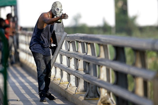 A demonstrator wearing a gas mask on a bridge at the Venezuela border with Colombia.