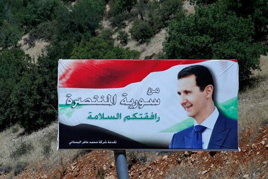 "A poster of Syrian President Bashar al-Assad with Arabic that reads ""Welcome to victorious Syria."