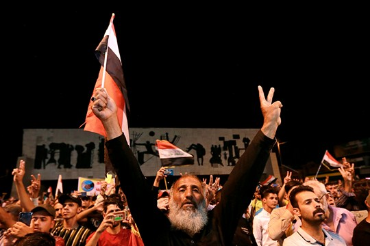Iraqi protesters chant slogans during a demonstration in Tahrir Square, in central Baghdad, Iraq.