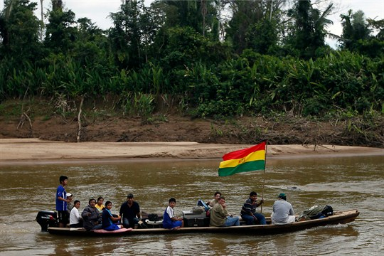 People, one carrying a Bolivian flag, in a boat at the Isiboro river, Bolivia.