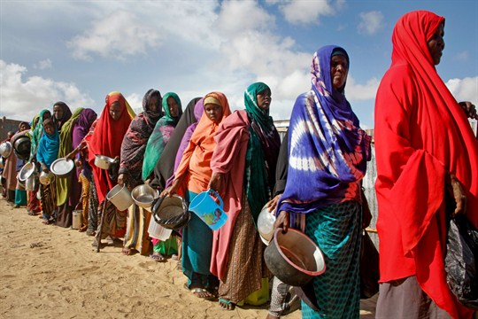 Women fleeing drought receive food outside of Mogadishu, Somalia.