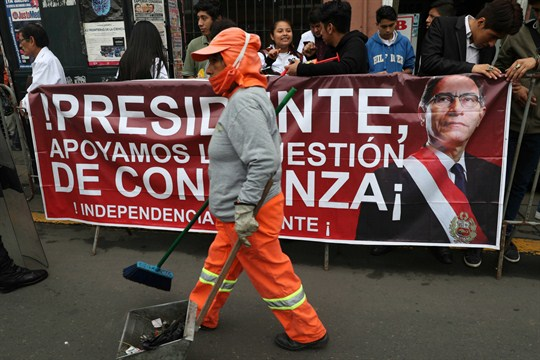 A street cleaner walks past a poster promoting Peruvian President Martin Vizcarra and his anti-corruption proposals.