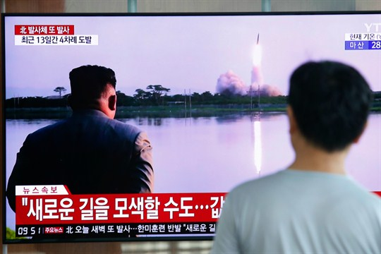 A man watches a TV showing an image of a North Korean missile launch.