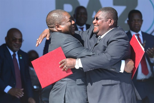 Mozambique's president, Filipe Nyusi, and Renamo leader Ossufo Momade hug after signing a peace accord.
